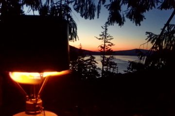 A brilliant sunrise is seen over Olallie Lake, OR while coffee boils on my camp stove.