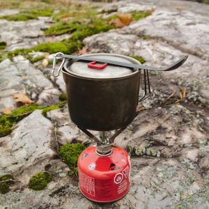 A stove, cook pot, spork, and fuel canister for backpacking.