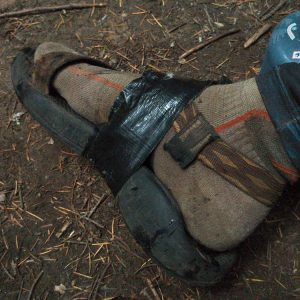 A taped up broken hiker sandal.